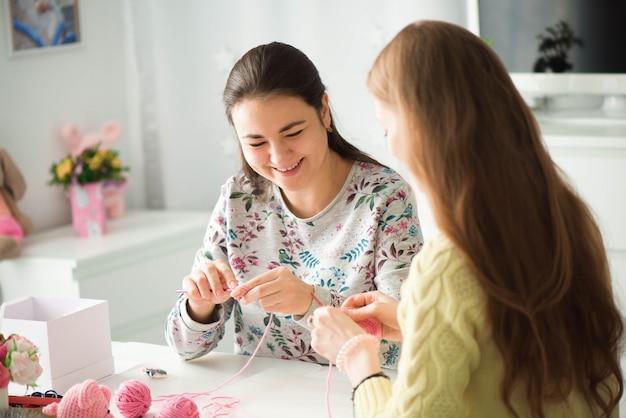 編み物レッスンの若い魅力的な女の子