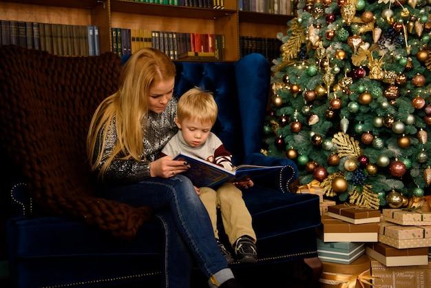 Счастливая семья, мать и ребенок, играя дома во время рождественских праздников