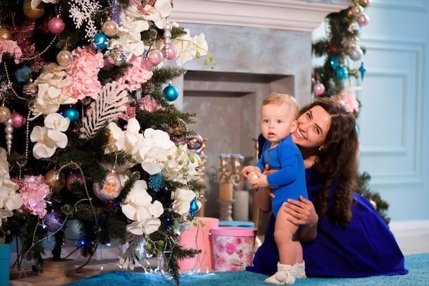 幸せな母と赤ちゃんはクリスマスを祝います。年末年始。