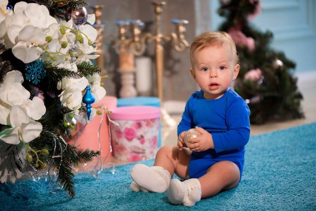クリスマスツリーの近くのカーペットの上に座っているかわいい男の子
