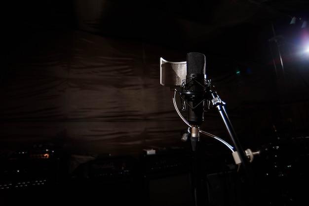 Закройте студийный конденсаторный микрофон с поп-фильтром и анти-ви