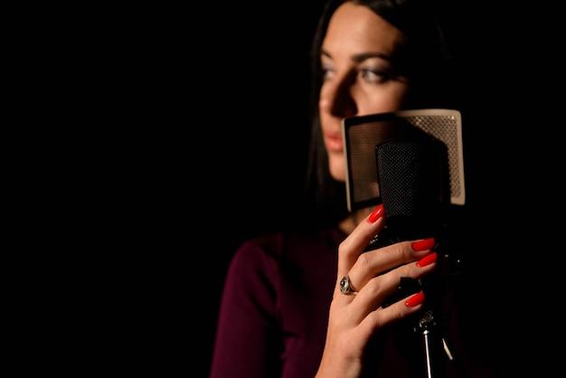 スタジオで新しい歌を録音するプロのミュージシャン。
