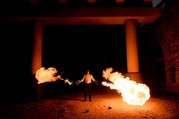 彼の手に火炎放射器と衣装のハロウィーン男。顔に悪魔の化粧