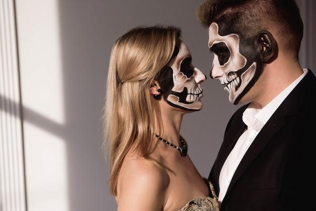 白い背景の上の暗い頭蓋骨化粧品をカップルします。ハロウィン