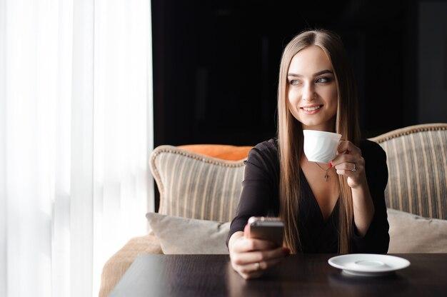 カフェでコーヒーを飲みながら携帯電話を使用しての若い女性。
