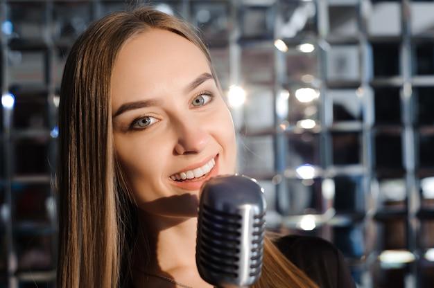 Красивая поющая девушка. красота женщины с микрофоном. гламурная модель певица. караоке песня.