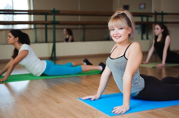 Женщина делает упражнения йоги в тренажерном зале, спорт фитнес девушка тренировки растяжения студии.