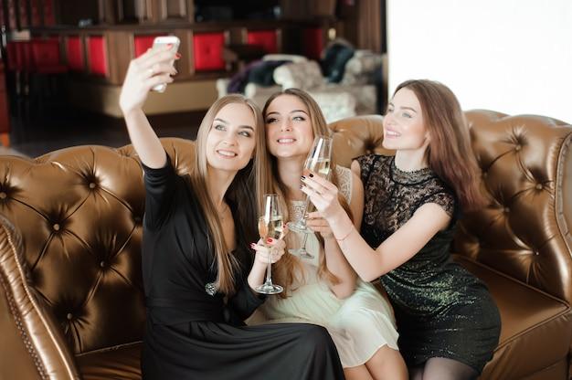 Три молодые девушки делают селфи фото в ресторане.