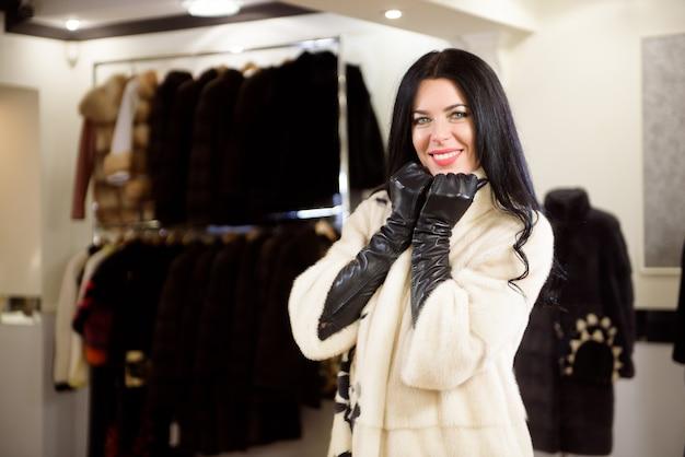Портрет привлекательной стильной женщины в меха в магазине.