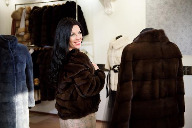 Зимняя красивая женщина в шубе. красота мода модель девушка в магазине меха.