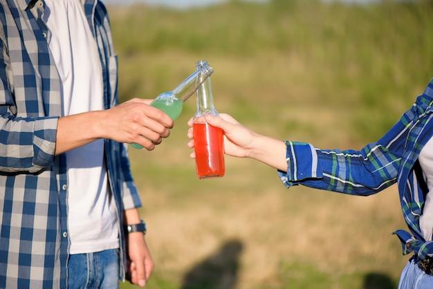 友達は笑顔で夕日を楽しみ、川の近くでカクテルを飲みます。