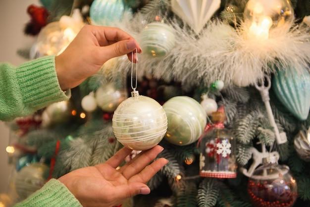 Счастливого рождества и счастливых праздников. девушка украшает елку в помещении