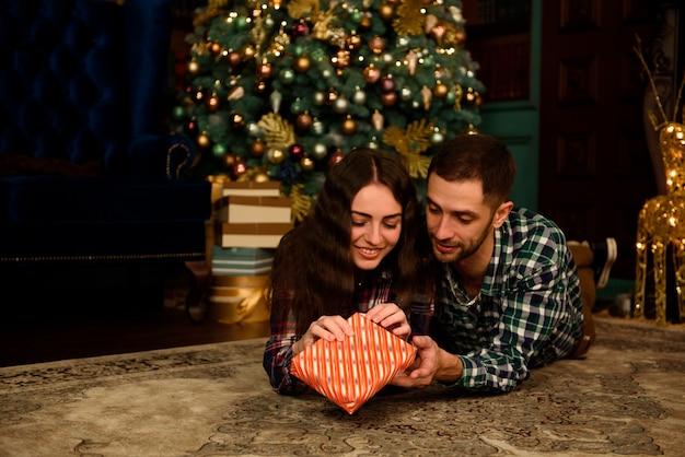 Пара с рождественским подарком дома на муке