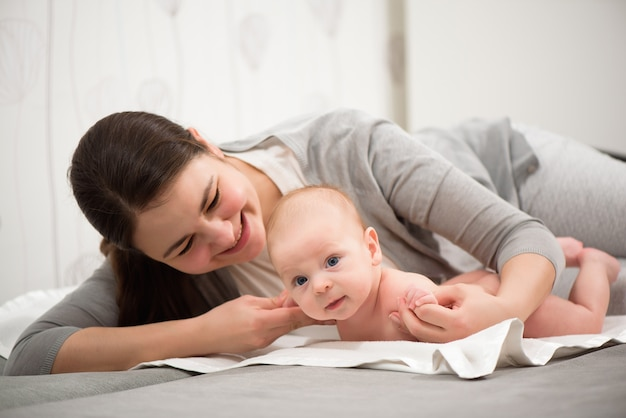 幸せな家族。母は寝室で赤ちゃんと遊ぶ。