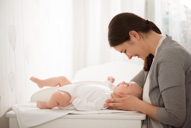 Молодая мать, держа ее ребенка в спальне.