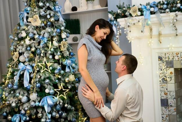 Концепция беременности, зимних отдыхов и людей - счастливая беременная жена с супругом дома на рождестве. молодая семья празднует рождество у себя дома.