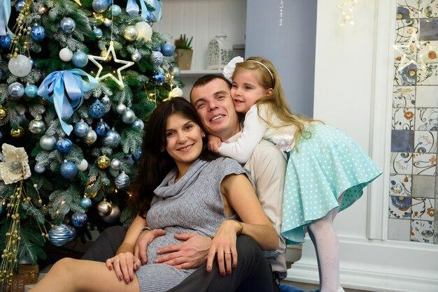 クリスマスの夜にカメラを見てフレンドリーな家族の肖像画。