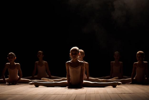 ストレッチとバレエダンスのためのトレーニングを持っているステージ上に座っているかなり若い女の子。
