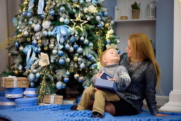 幸せな家族の母親と赤ちゃんの幼い息子がクリスマス休暇で家で遊んで。年末年始