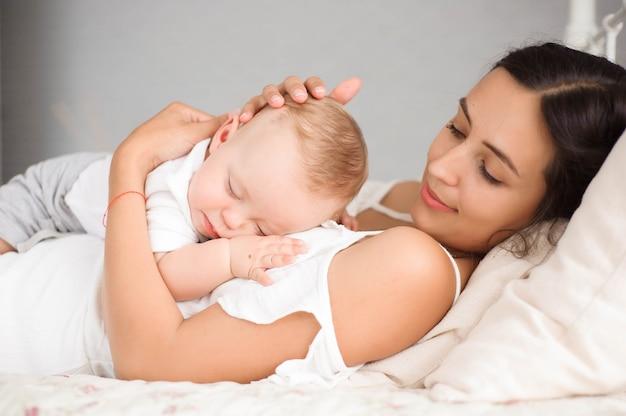 母親と一緒にベッドで寝ているかわいい男の子