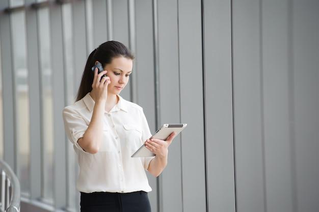 Молодая коммерсантка говоря на мобильном телефоне пока готовящ окно в офисе. красивая молодая женская модель в офисе.