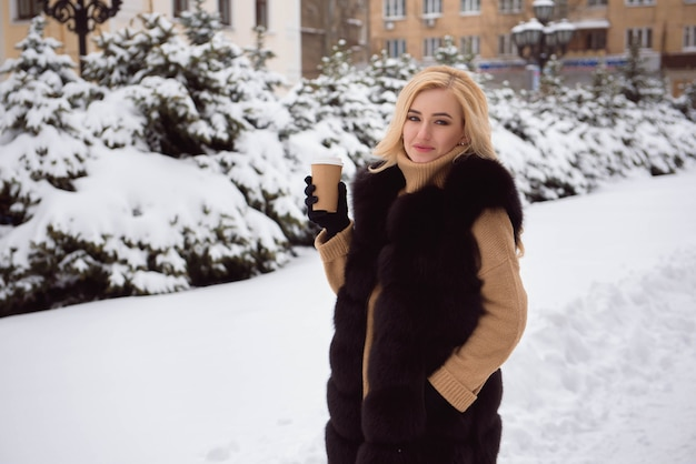 Портрет кофе европейской модной женщины стиля выпивая в парке зимы.