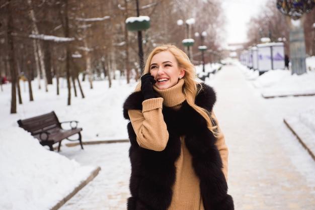 冬の通りを歩いて美しい幸せな笑みを浮かべて少女の写真を屋外のクローズアップ