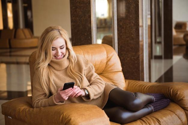 Привлекательная женщина имеет перерыв на кофе, используя ее мобильный телефон.