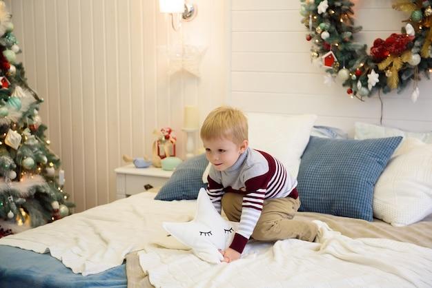 Счастливый маленький мальчик прыгает на кровати. маленький мальчик с удовольствием празднует рождество дома