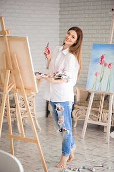 女性は彼女のスタジオで油絵の具でキャンバスに絵を描く