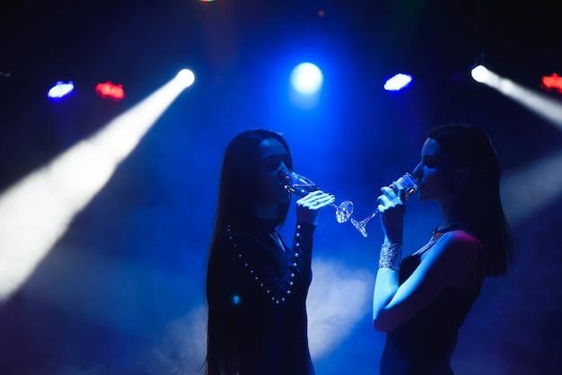 Юные друзья танцуют с бокалами шампанского в руках