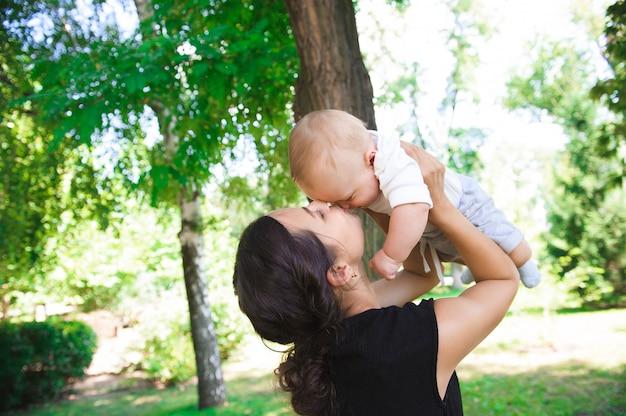 Счастливая мать и дочь смеются вместе на открытом воздухе.