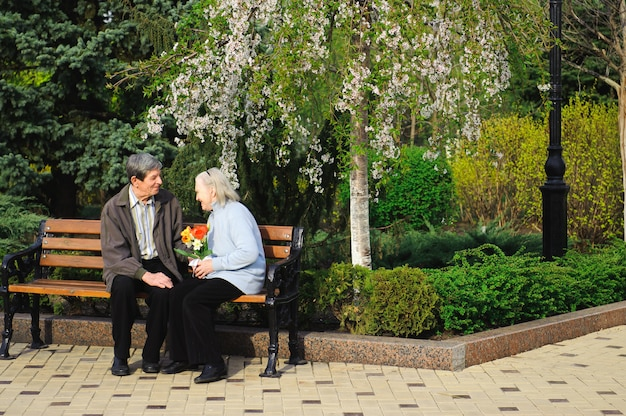 Красивые счастливые старые люди, сидя в осенний парк.