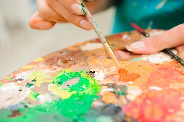 Красивая молодая девушка рисует картину красками на уроке искусства