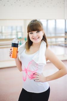 健康的な女性はフィットネスで水を飲む