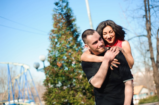 市では屋外ポーズ愛の若い美しいカップル。若い女性が彼女のハンサムな男と笑っています。