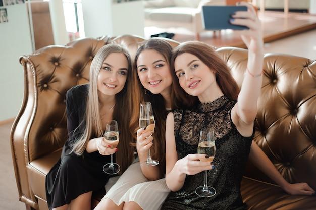 Три молодые девушки делают селфи фото в ресторане