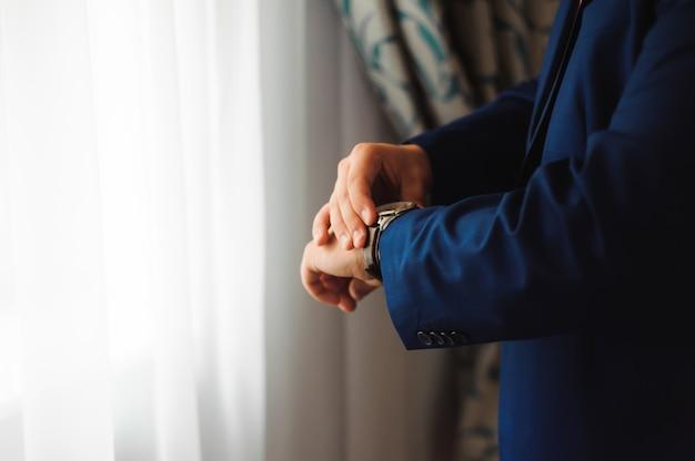 パートナーと会う前にエレガントなビジネスマン服を着て時計