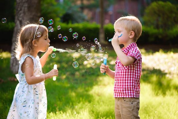 子供と友達が夕日と遊び場でバブルを再生します。