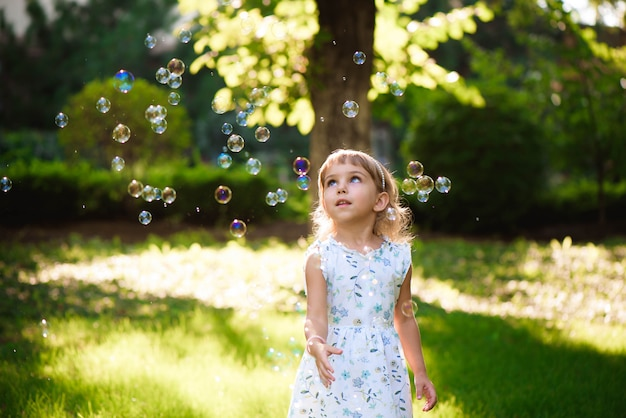 タンポポと草の中に立って幸せな赤ちゃん女の子