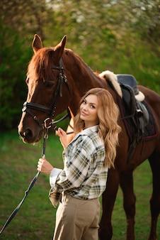 Девушка с ее лошадью и красивым теплым лесом захода солнца весной.