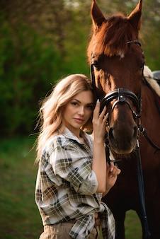 Молодая женщина представляя с коричневой лошадью в лесе в солнечном луге.