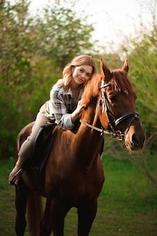 Красивая девушка верхом на лошади в сельской местности