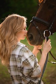 Красивая девушка вместе со своей любимой каштановой лошадкой.