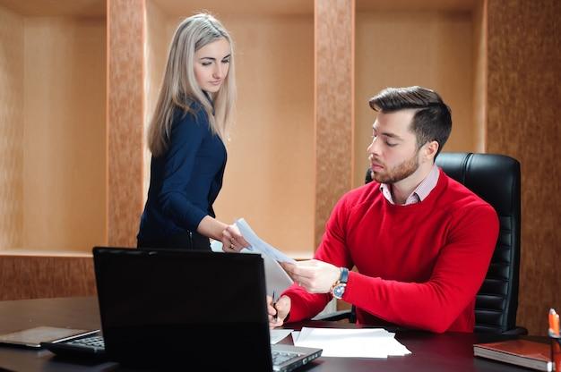 コンピューターの前のテーブルに座っているビジネスパートナー