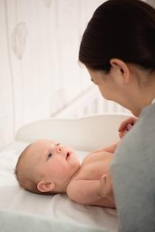 ママの赤ちゃん。女性と生まれたばかりの少年は白い寝室でリラックスします。自宅で家族。