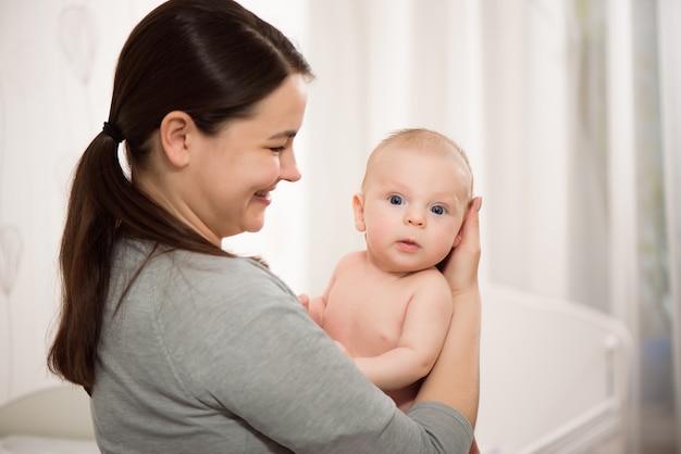 若い母親が彼女の生まれたばかりの子供を抱き締めます。愛、信頼、優しさの概念。保育園のための寝具と繊維。