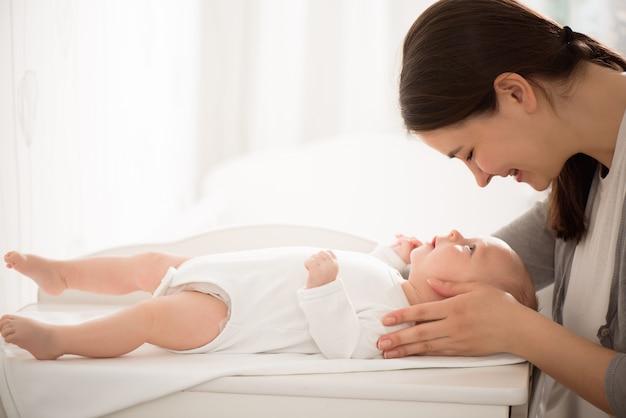 若い母親が寝室で彼女の赤ん坊を保持しています。