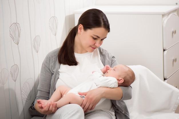 若い母親が彼女の生まれたばかりの子供を保持しています。ママの赤ちゃん。女性と生まれたばかりの少年は白い寝室でリラックスします。