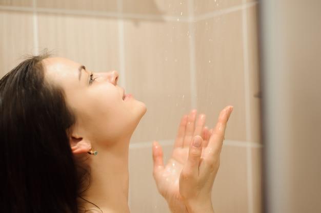 リラックスしたシャワーを浴びている若い美しい女性の写真